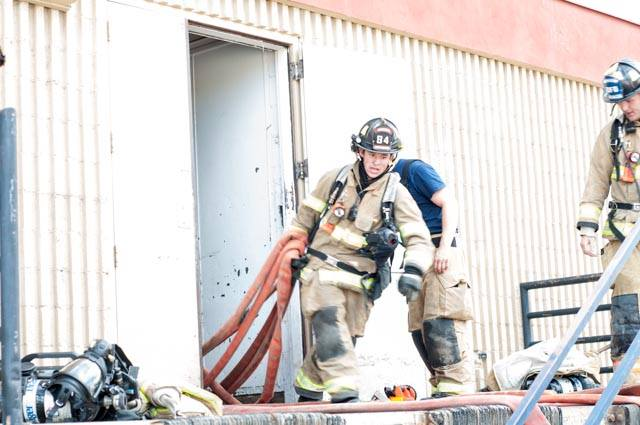 Firefighter coming out of building with hose