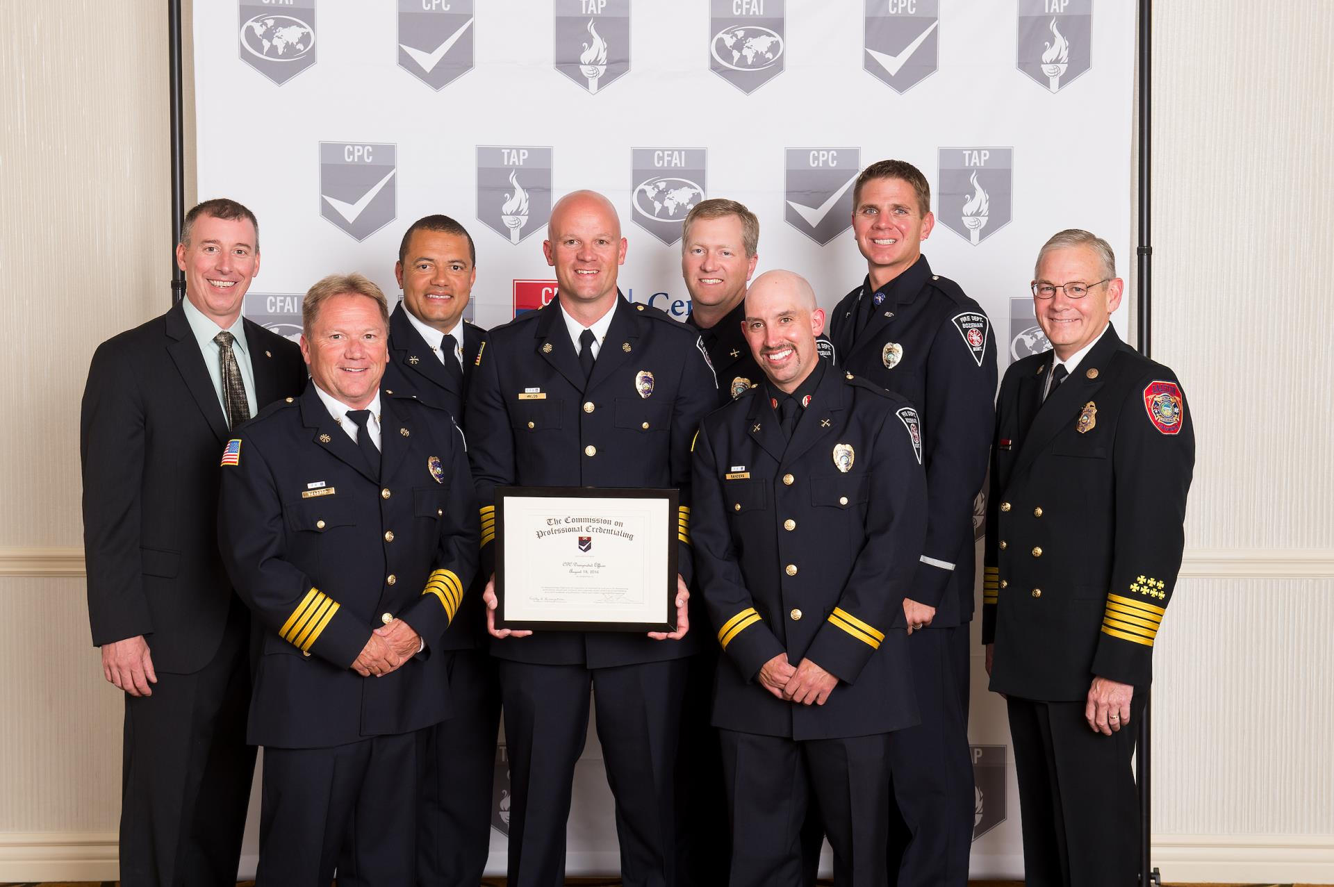 Eight firefighters wearing class A's recieving awards
