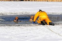 Firefighter resuce dogs in semi frozen body of water