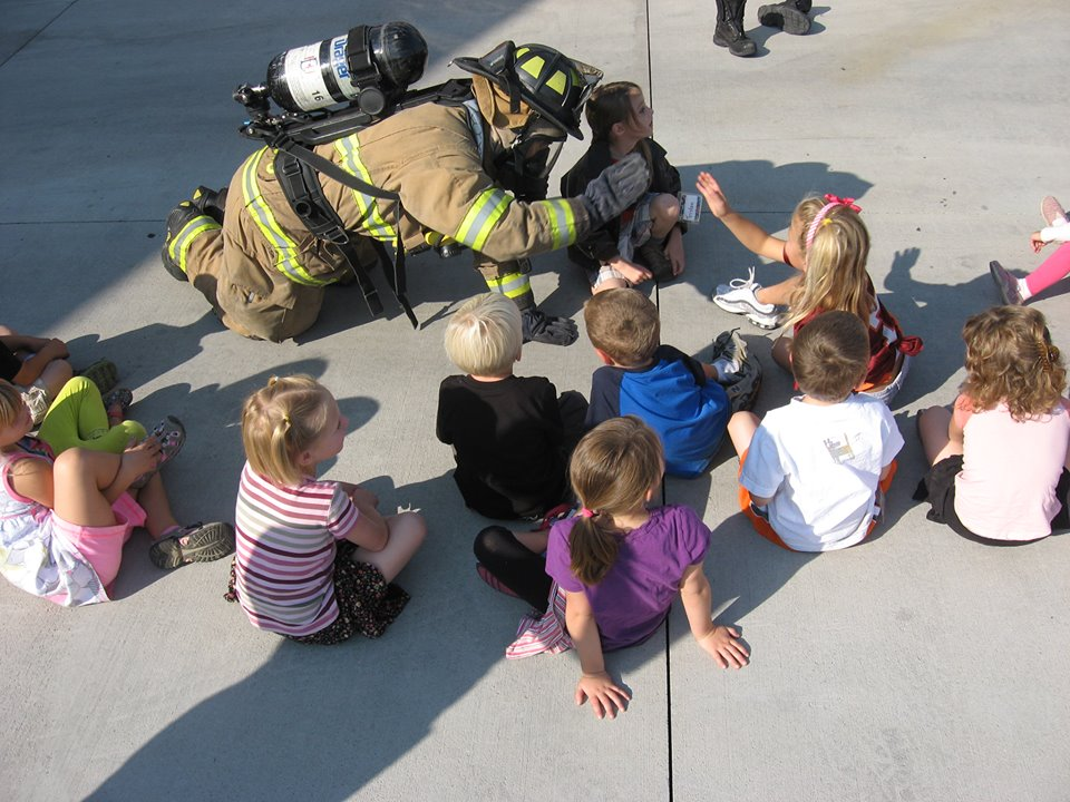 Firefighter in turnout gear giving kids high fives
